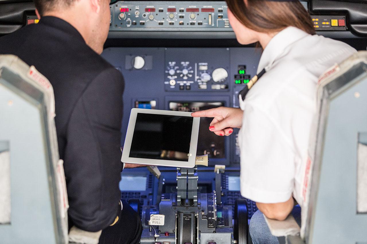 Pilot and Copilot Checking Flight Information on Digital Tablet
